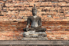 A stone statue of Buddha was installed in front of a brick wall in a park in Sukhothai (Thailand) Stock Photography