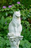 Stone Statue of a Cat. The cat seems to watch out the garden. Rhododendron flowers were blooming in the back Royalty Free Stock Image