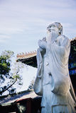 Stone statue of Confucius, traditional pagoda in the background Stock Photography