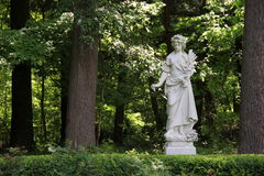 Stone statue displayed in Yaddo Gardens, Saratoga Springs,New York,Summer,2013. Gorgeous stone statue of woman in long robes and bare feet holding arrangement of Royalty Free Stock Photos