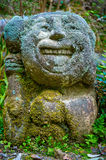 STONE STATUE - THE HAPPY FACE. A Statue sculpted in stone with smiling face. It is old and eroded through time. The whole statue is covered in moss and tiny Stock Photography