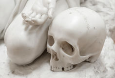 Stone statue of human skull with hand stock images