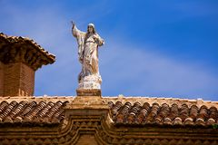 Stone statue of Jesus on a tile roof in Granada Stock Photos