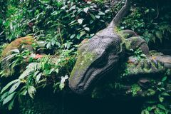 Stone statue of lizard in leaves. A stone statue of a lizard in the leaves looks down Stock Photo