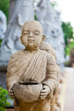 Stone statue of a novice. Stock Image