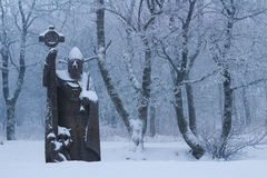 Stone statue Saint Kilian in snowy forest Stock Photography