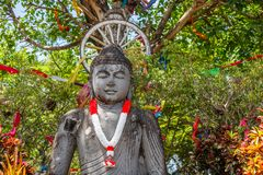Stone statue of Sitting Buddha with with a garland in red and white colors of Indonesian flag for Indonesia Independence Day. Stone statue of Sitting Buddha royalty free stock photos