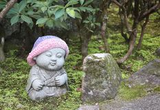 Stone statue of smiling Jizo in a knitted hat, Miyajima, Japan royalty free stock images