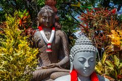Stone statues of Sitting Buddha with with garlands in red and white colors of Indonesian flag for Indonesia Independence Day. Stone statues of Sitting Buddhas royalty free stock photos