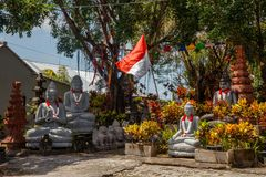Stone statues of Sitting Buddha with with garlands in red and white colors of Indonesian flag for Indonesia Independence Day. Stone statues of Sitting Buddhas stock photography