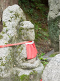 Stone status with red cloth. Kyoto,Japan - June 28, 2014 : stone status with red cloth at Kyomizu Temple built in 1633, is one of the most famous landmark of Stock Photos