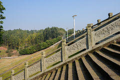 Stone steps and balustrade on woody dam in sunny winter Stock Images