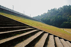 Stone steps and grassy lawn on slope of dam in sunny winter Royalty Free Stock Image