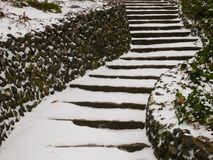 Steps and Stone Walls in the Snow. Stone steps leading upwards in the snow with stone walls on either side Stock Photo