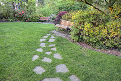 Stone Steps to Park Bench. Natural Stone Steps on Green Grass Lawn to Park Bench royalty free stock photos