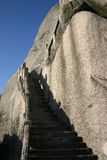 Stone steps up mountainside. Stone steps leading up smooth mountainside with blue sky background Royalty Free Stock Photography