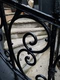 Stone steps visible through decorative intricate iron railing. Curved S pattern in iron weathered over time, classic old metalwork. Curved stone steps show wear royalty free stock images