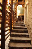 Stone steps and wooden handrail. Restored stairway. Architectural detail of a stone staircase and a wood log handrail. Modern mountain architecture in the stock images