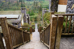 Stone steps with wooden handrails between houses in mountain aft Royalty Free Stock Images
