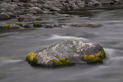 Stone streamlined water in the river. Long exposure shot. Peninsula Kony. Magadan Region. Russia Royalty Free Stock Photos