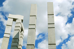 Stone structures. Two pylons and a three-legged arch under a blue sky with white clouds Stock Images
