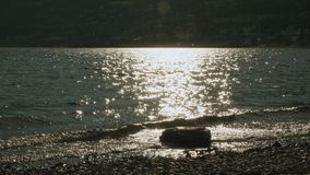 Stone and sun reflection on the lake stock video