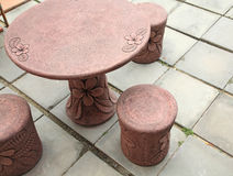 Stone table and chairs with floral pattern Stock Photo