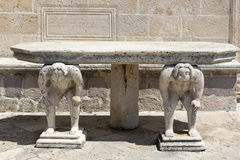 Stone table with male figures near the church on the island of Gospa od Skrpela in the Boko-Kotorsky Gulf. PERAST, MONTENEGRO - AUGUST 04, 2017:Stone table with stock photos