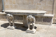 Stone table with male figures near the church on the island of Gospa od Skrpela in the Boko-Kotorsky Gulf. PERAST, MONTENEGRO - AUGUST 04, 2017:Stone table with royalty free stock photos
