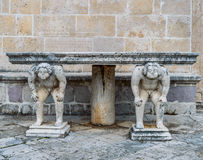 Stone table which stands on two carved titans Stock Photos