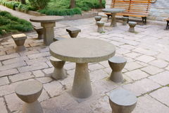 Stone tables and chairs. Tables and chairs in a park at afternoon Royalty Free Stock Images