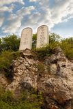 Stone tablets on a rocky hill with carved 10 commandments. Ten Commandments List. Stone tablets on a rocky hill with carved 10 commandments royalty free stock photos