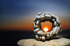 Stone Telescope. Sunset review through hole the stone ball Royalty Free Stock Photography