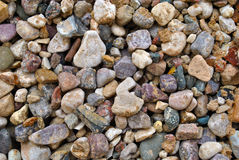 Stone texture. Colorful stones on the sand background Stock Photography