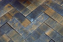 Stone texture from a fragment of gray brown paving tiles on the road Stock Photos