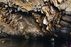 Stone texture inside cave and rowing woman row a boat with tourist at Trang An Grottoes in Ninh Binh, Vietnam Royalty Free Stock Photo