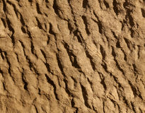 Stone texture. Yellow textured stone, sandstone, that has been weathered. Erosion creating the undulating texture with diagonal lines Royalty Free Stock Photography