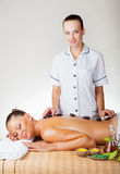 Stone-therapy. Beautiful young women with closed eyes get a relaxing massage Royalty Free Stock Image