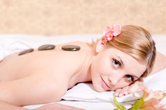 Stone therapy massage: young attractive blond woman having fun enjoying spa procedures stone therapy massage & aromatherapy Stock Photo