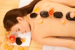 Stone therapy. Woman getting a hot stone massage at spa salon.  Stock Photo