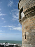 Stone tower. Old stone tower in front of the sea with cloudy sky Royalty Free Stock Image
