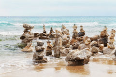 Stone tower against blue sea background for balance, meditation and zen theme. Stock Photos