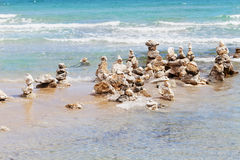 Stone tower against blue sea for balance, meditation and zen theme. Royalty Free Stock Photos
