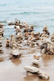 Stone tower against sea background for balance, meditation and zen theme. Stock Photos