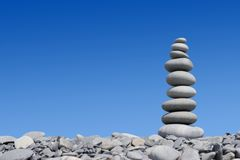 Stone tower on the blue background. Sea stones on the beach Royalty Free Stock Photography