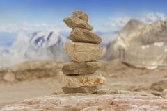 Stone tower in mountains height show balance stability power. Stones stack in mountain panorama with blue sky visualizes creativity, consulting, success or Stock Photo