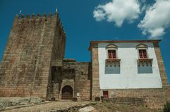 Stone tower over rocky hill at the medieval Belmonte Castle. Stone walls and square tower over rocky hill in a sunny day, at the front facade of medieval royalty free stock images