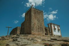 Stone tower over rocky hill at the medieval Belmonte Castle. Stone walls and square tower over rocky hill with wooden cross, in a sunny day at the medieval stock image