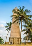 Stone tower and palm trees on the beach Royalty Free Stock Photos