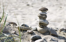 Stone tower and plants on a natural sandy beach Royalty Free Stock Photography